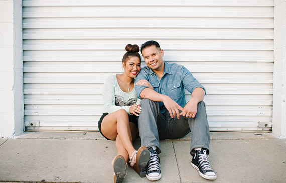 Portrait of an engaged couple sitting infront of the white garage door.