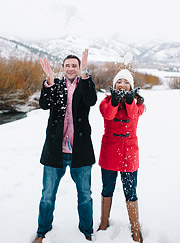 Engagement photography. Couple laughing and throwing snow above their heads
