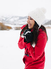 Cute girl wearing a red coat in the snow making a snowball. Editorial engagement photography