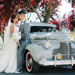 Bride and groom portrait in front of a gray 1940 Chevy classic car.