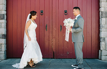 Bride dancing for the groom in front of red barn doors in Rios-Lovell Winery