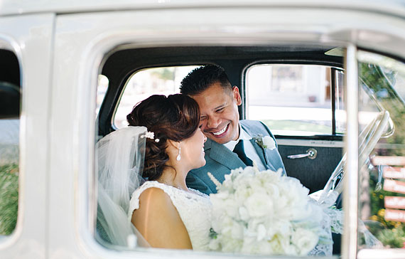 Bride and groom inside of the gray 1940 Chevrolet classic car.