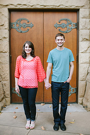 Portrait of a couple in front of the wooden doors of Stanford Memorial Church on Stanford University campus.