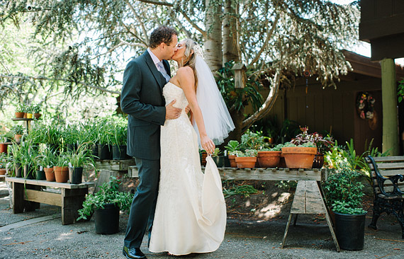 Bride and groom kissing in the plant nursery. San Mateo Garden Center wedding.