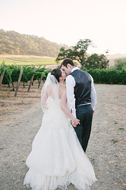 Bride and groom walking and kissing in the vineyard