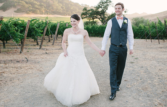 Bride and groom walking holding hands in a vineyard