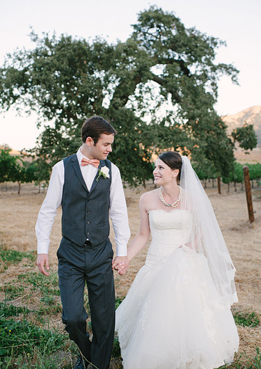 Bride and groom walk in the vineyard of Clos LaChance Winery