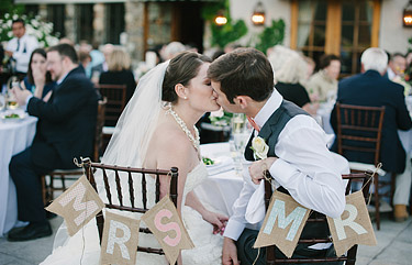 Mr. and Mrs. signs on the chairs. Bride and groom kissing at Clos LaChance Winery