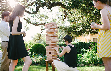 Wedding reception guests playing the giant life-size Jenga