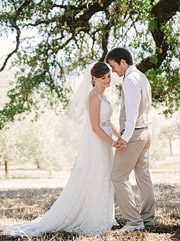 Bride and groom holding hands under an oak tree.