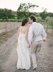 Bride and groom walking down the dirt road kissing.