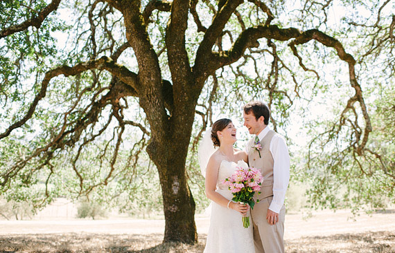 Bride and groom laughing underneath a huge oak tree. Beltane Ranch wedding photos.