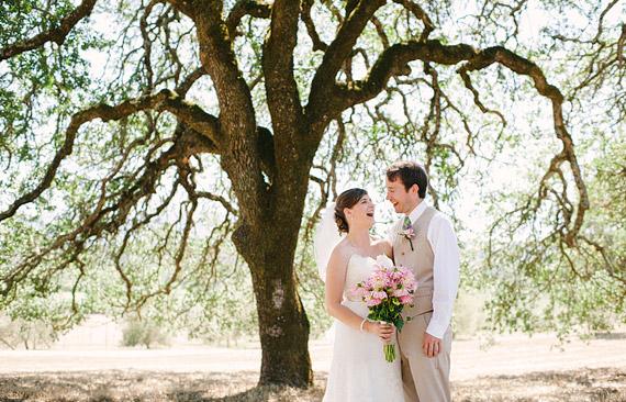 Bride and groom laughing underneath a huge oak tree. Beltane Ranch wedding photos.