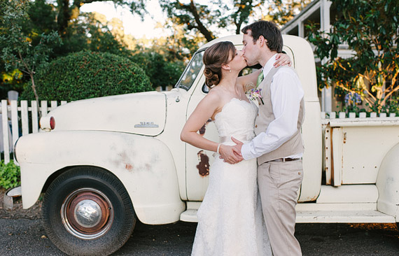Bride and groom kissing in front of the old Chevy truck at Beltane Ranch.