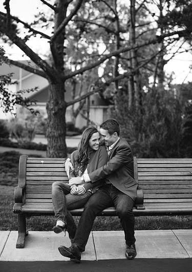 Couple sitting cuddled up on a park bench. Black and white