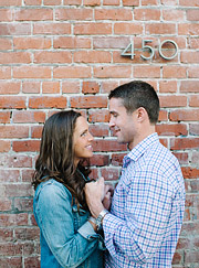 Portrait of engaged couple in front of brick building. San Francisco portraits.