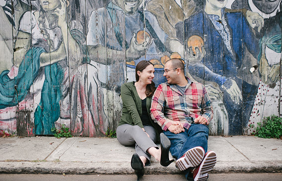 Couple sitting on the sidewalk with mural in the background