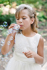 Flower girl blowing bubbles during ceremony at Nestldown