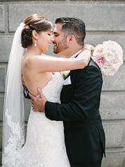 Portrait of bride and groom huggin each other at the Music Concourse in Golden Gate Park. Greek wedding in San Francisco.