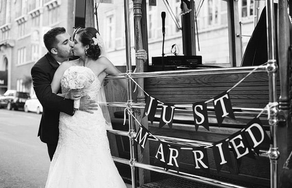 Bride and groom kissing on cable car in San Francisco with Just Married sign