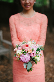 Bridesmaid in peach dress holding flowers by Twig and Petals