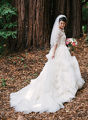 Bride fixing her dress with redwood trees behind her