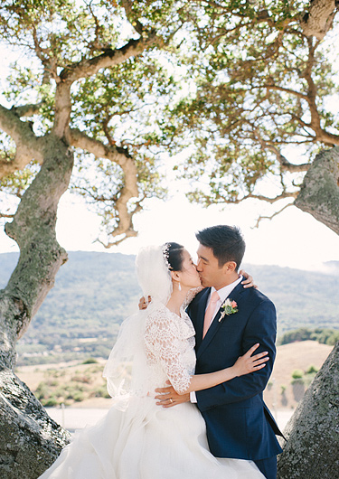 bride and groom kissing between trees