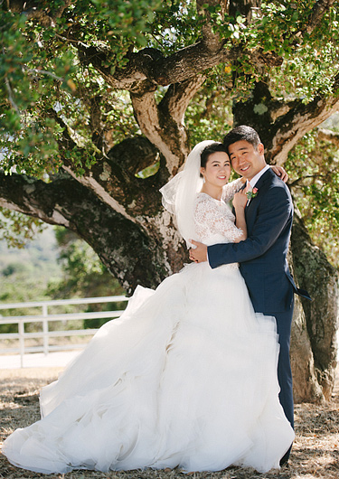 bride and groom embracing in front of tree