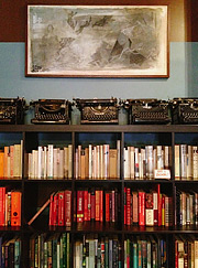 Typewriters on the shelf with books.