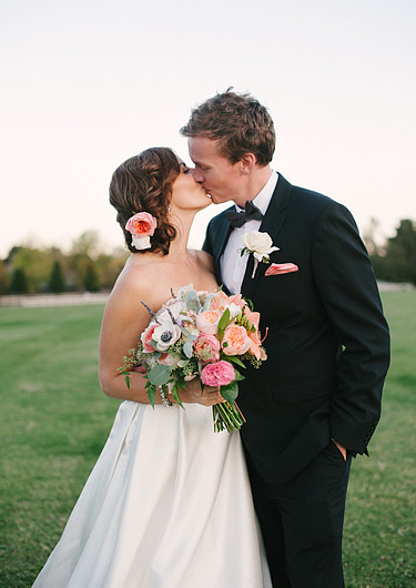 Romantic portrait of the bride and groom kissing on the polo field
