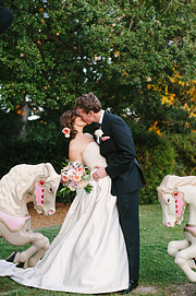Bride and groom kissing with the playground horses in the background