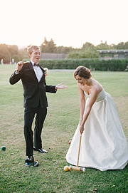 Bride and groom playing Croquet in the field