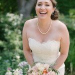 Portrait of a bride holding her bouquet of flowers laughing. Outdoor Art Club Wedding in Mill Valley