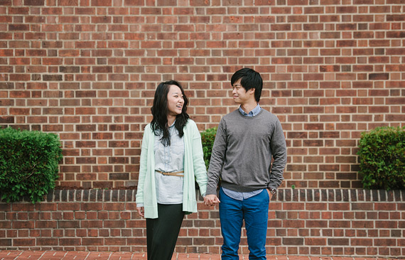 Portrait in front of a brick wall. Old Town Alexandria engagement photos.