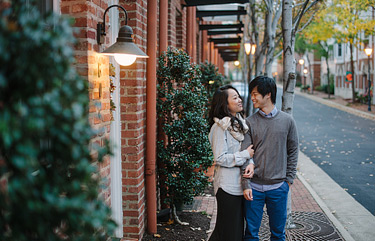Couple standing side by side on a street. Old Town Alexandria engagement photos.