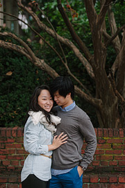 Portrait of a couple with tree branches and brick in the background. Old Town Alexandria engagement photos.