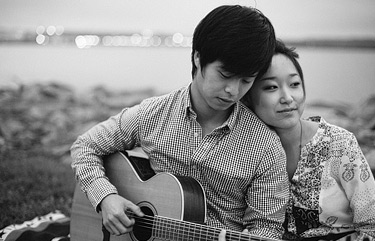 Playing guitar for his love cuddled up on a blanket. Old Town Alexandria engagement photos.