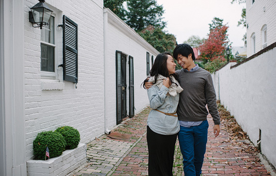 Walking side by side with arms around each other in an old Virginia alley. Old Town Alexandria engagement photos.