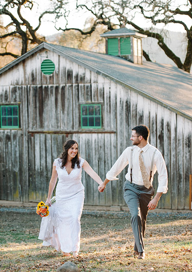 Bride and groom walking together with old barn in the background