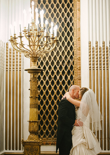 Bride and groom kissing next to a chandelier at Westin St. Francis. Wedding photography by Pictilio