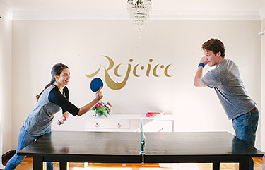 Couple playing table tennis at home on the dining room table