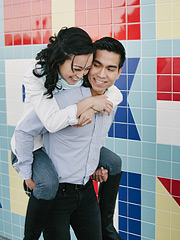 Piggy back ride in front of a colorful wall. Engagaement photography by Pictilio.