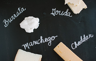 Cheese board with names of cheeses written in chalk