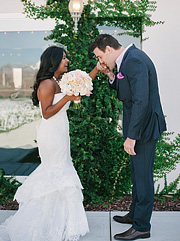Groom kissing bride's hand.