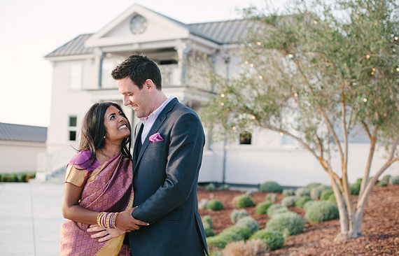 Portrait of bride and groom in front of Willow Heights Mansion. Multicaultural wedding. Bride is wearing sari.