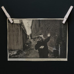 Old black and white photograph cut out from the newspaper of a couple dancing in an alley.
