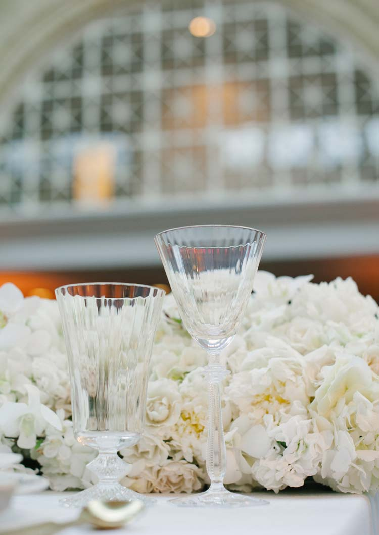 A table with glasses and white flora centerpiece at San Francisco Ferry Building. Wedding photography by Pictilio.