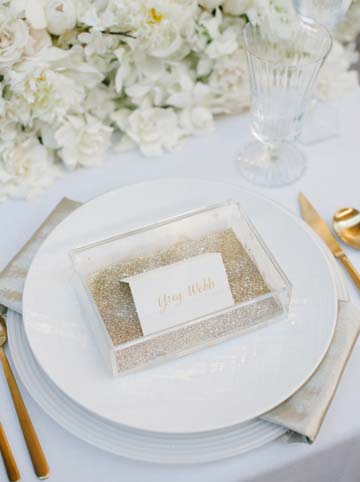 Clear acrylic box with white place card and gold sequin