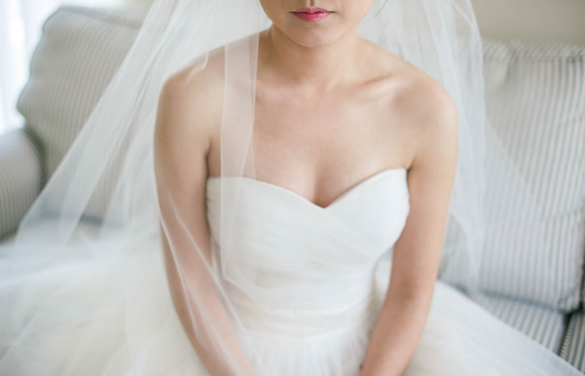 Bride, gown, veil and pink lipstick. Romantic wedding photography.