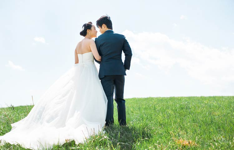Bride and groom against a pale blue sky. Maryland wedding portraits of bride and groom.